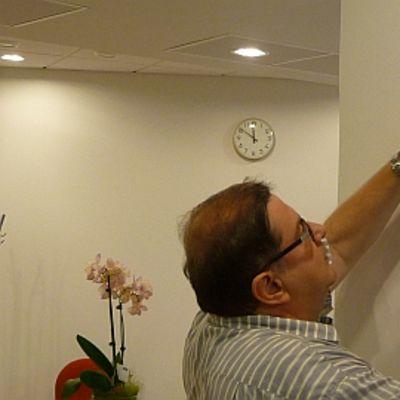Pertti Rajala asettaa vaakunaa seinälle.
