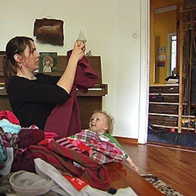 perheenäiti viikkaa pestyjä vaatteita pienen lapsen kanssa.