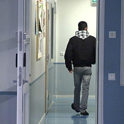 Maahanmuuttaja kävelee vastaanottokeskuksen käytävällä.