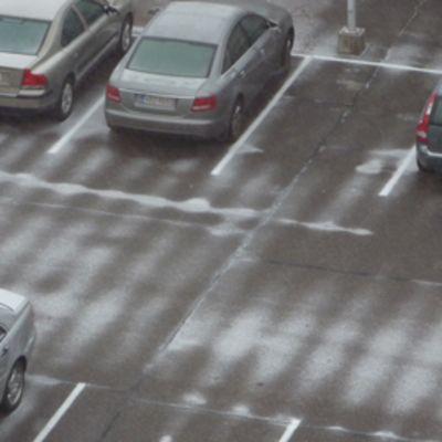 Ohut lumipeite parkkipaikalla.