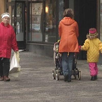 Vanhus ja lapsiperhe ohittavat toisensa kadulla.