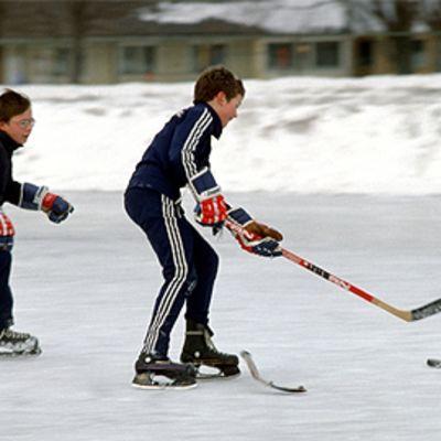 Kaksi poikaa pelaa jääkiekkoa luistinradalla.