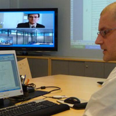 Kuvassa mies tietokonepäätteen ääressä taustalla televisioruudulla videoneuvotteluyhteydessä toinen mies.