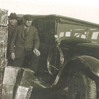 Kuvassa pirtukanistereita, auto ja kaksi miestä. Takavarikoitu spriilasti odottaa jatkokuljetusta vuonna 1930.