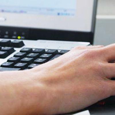 Käsi kannettavan tietokoneen vieressä hiirellä.