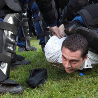 Mellakkapoliisit pidättävät miestä nurmikolla.