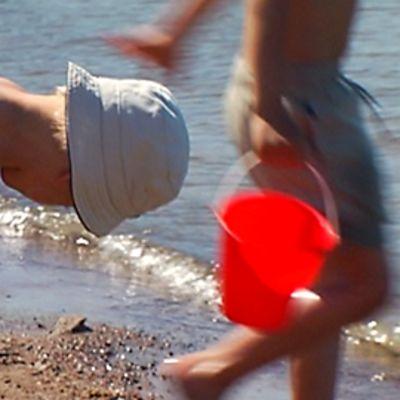 Lapsi leikkii helteisellä uimarannalla.