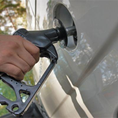 Käsi pitelee tankkauspistoolia bensatankin aukossa