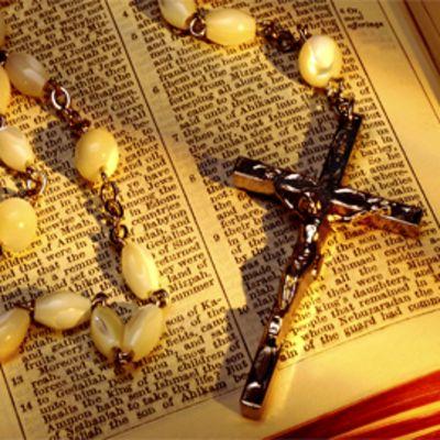 Metallinen krusifiksi ja rukousnauha raamatun päällä.