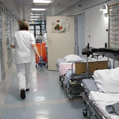 Hoitaja kävelee sairaalan käytävällä.
