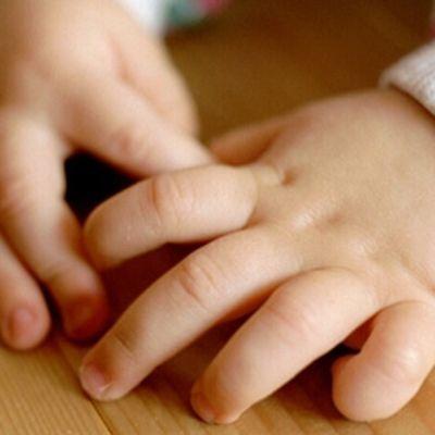 Lapsen kädet pöydällä