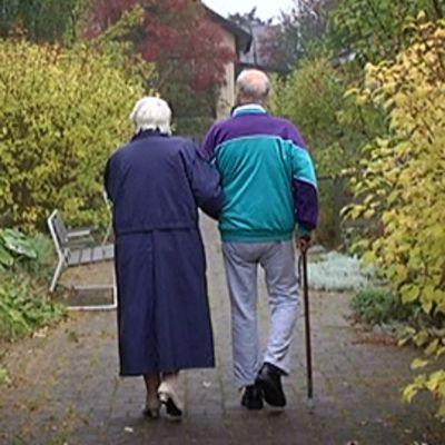 Kaksi vanhusta kävelyllä hoitokodin pihalla