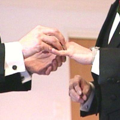 Tummaan pukuun pukeutunut mies pujottaa toisen sormen mieheen vihkisormusta.