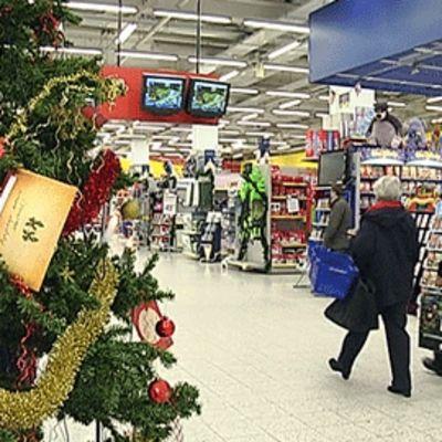 Asiakkaat kävelevät joulukuusen ohi supermarketissa.