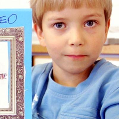 Poika näyttää tekemäänsä isänpäiväkorttia.