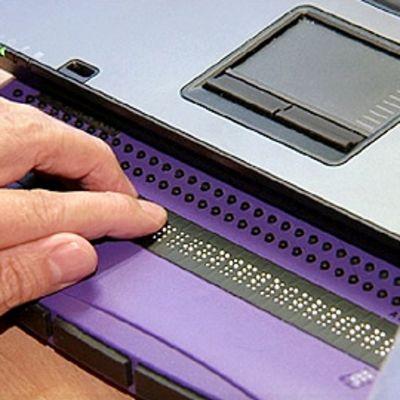 Näkövammainen  käyttää tietokoneen pistekirjoitusnäyttöä.