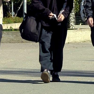 Kolme nuorta miestä kävelee kadulla.
