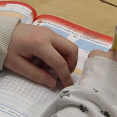 Ala-asteen oppilas tekee matematiikan tehtäviä.