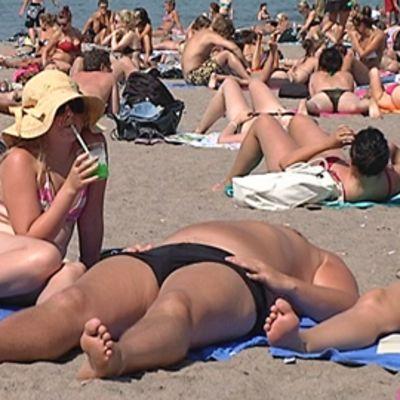 Ihmisiä ottamassa aurinkoa hiekkarannalla.