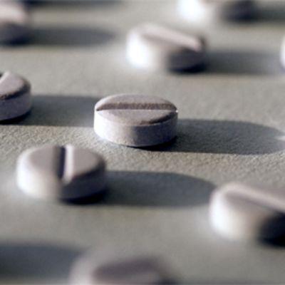 Valkoisia lääketabletteja paperin päällä.