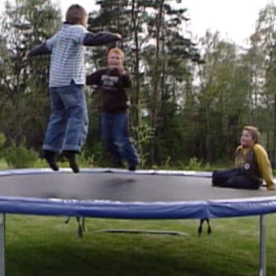 Pojat pomppivat trampoliinilla