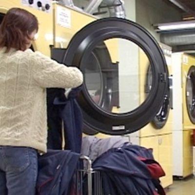 Nainen täyttää suurta pesukonetta