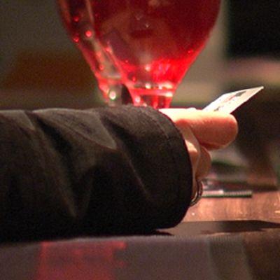 Käsi baaritiskillä. Kädessä  luotto- tai pankkikortti. Taustalla kaksi juomalasia.