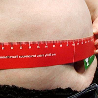 Nainen mittaa vyötärönsä ympärysmittaa.