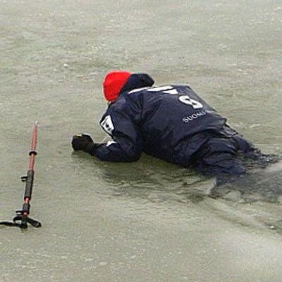 Jäihin pudonnut mies kapuaa jään pinalle naskalien avulla. Lavastettu tilanne.