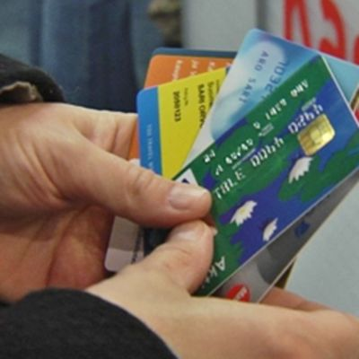 Henkilö katselee maksukorttejaan kassalla.