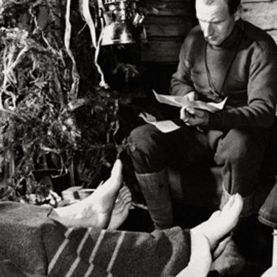 Sotilas lukee kirjettä korsussa jouluna 1939