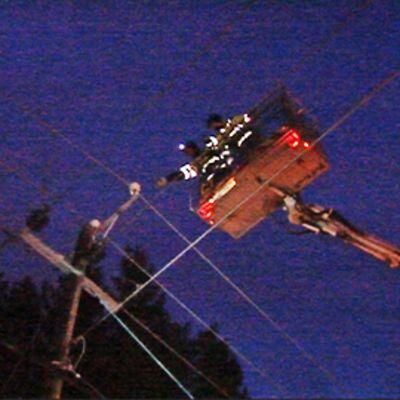 Kaksi sähkömiestä nosturissa.