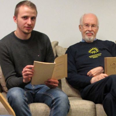 Kuvassa kaksi miestä istuu sohvalla vanhojen kirjojen kanssa