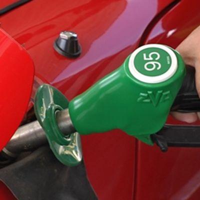 Mies tankkaa punaiseen autoonsa 95-oktaanista bensiiniä.