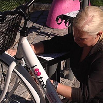 Projektipäällikkö Saara Saarteinen lukitsee kaupunkipyörän telineeseen.