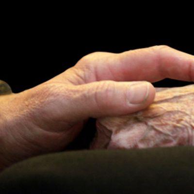 Mies taputtaa vanhuksen kättä.