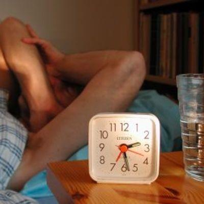 Uneton mies yöllä sängyssä. Herätyskello ja vesilasi yöpöydällä.
