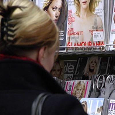 Nainen katselee lehtiä kioskilla