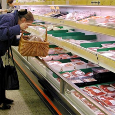 Nainen tutkii lihatuotteita marketin tiskillä.