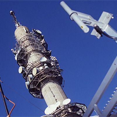 Yleisradion linkkitorni ja antenneja etualalla. Taustalla sininen taivas.