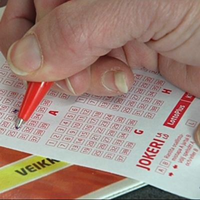 Kynä kädessä. Täyttää lottokuponkia.