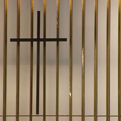 Musta risti näkyy kullankeltaisen, läpinäkyvän pystypaneelirivistön takaa.