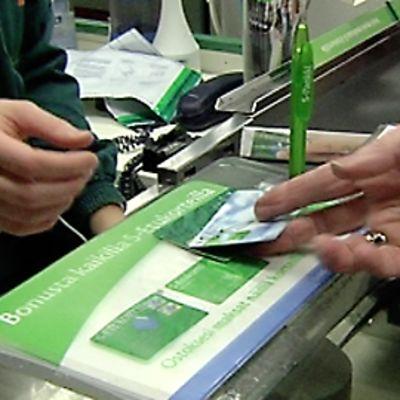 Bonuskortteja kaupan kassalla.