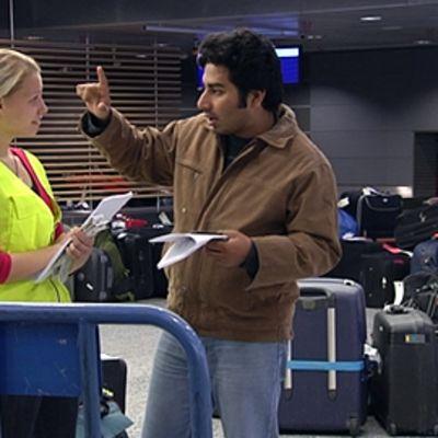 Ulkomaalainen mies keskustelee lentokenttätyöntekijän kanssa