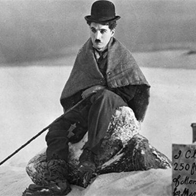 Charles Chaplinin kulkurihahmo istuu lumessa, vierassä kyltti kertoo hänen vallanneen maata kaivosta varten.