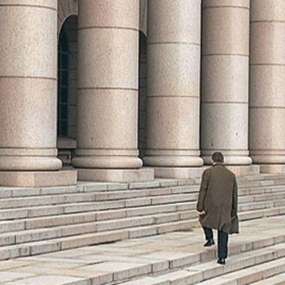 Mieshenkilö nousee eduskuntatalon portaita.