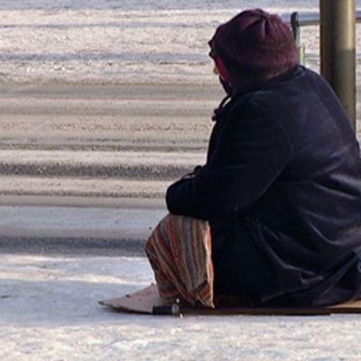 Romaninainen kerjää talvisessa Hakaniemessä Helsingisssä.