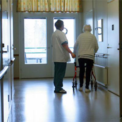 Hoitaja taluttaa rollaattorin avulla kulkevaa vanhusta