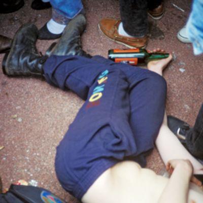 Päihtynyt nuori mies makaa maassa ihmisjoukossa.