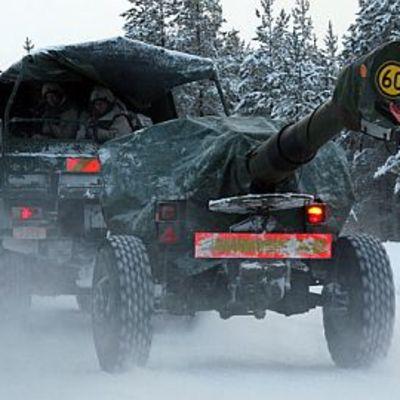Kuorma-auto vetää tykkiä talvisella tiellä